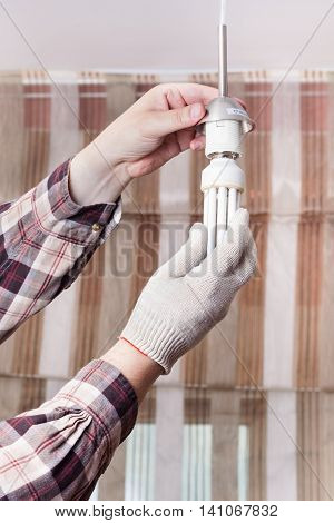 Electrician Mounts Fluorescent Lamp In Lampholder