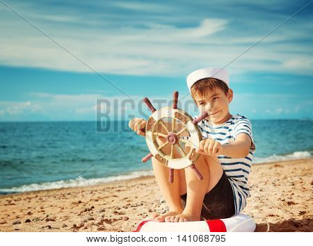seven years old boy playing at the beach in sailor hat. Child with a steering wheel at sea