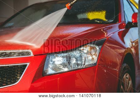 Contactless car wash self-service. Young man washing his car