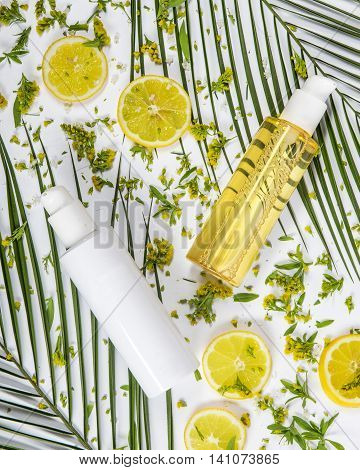 The bottle of brightening tonic and the bottle of brightening cosmetic milk on the nature palm leaves background with lemon slices and small yellow flowers