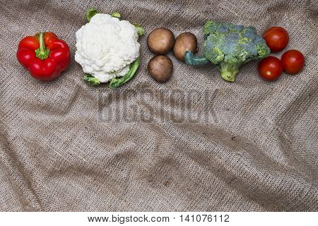 Fresh vegetables line on rustic homemade sackcloth background