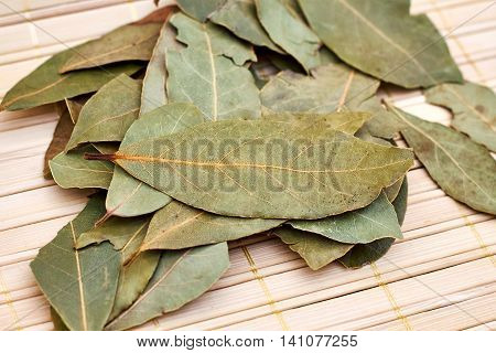 Dry bay laurel leaves on bright wooden background