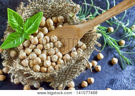 Garbanzo beans (chickpeas) and wooden spoon with basil in small burlap bag on dark rustic background. Top view with copy space