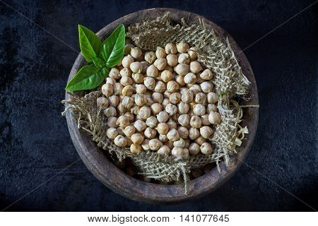 Garbanzo beans (chickpeas) with basil in clay bowl on black rustic background. Top view