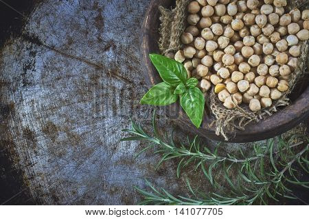 Garbanzo beans (chickpeas) with basil in clay bowl on metallic rustic background. Top view with copy space
