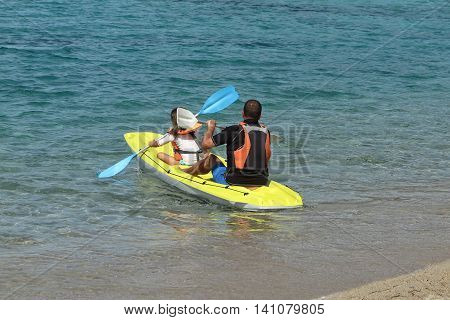 Daughter And Father Exploring Calm Tropical Bay By Kayak. Back View.