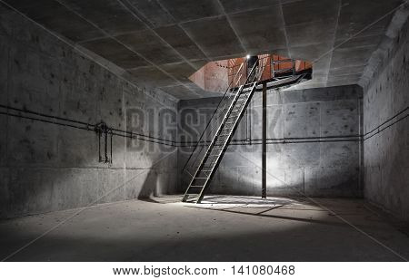 Concrete room under ground with a ladder to the surface from which the light comes. Technical room ventilation shaft of the underground facility