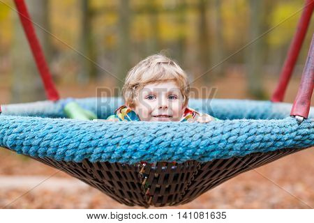 Preschool little kid boy having fun with chain swing on outdoor playground. child swinging on warm sunny autumn day. Active leisure with kids. Boy wearing colorful clothes