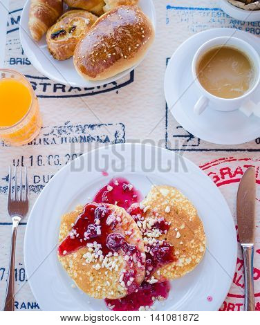 Breakfast including pancakes with raspberry jam, coffee with milk and pastries. Healthy breakfast. Good morning. Breakfast table. Morning breakfast with classic pancakes and jam. Top view.