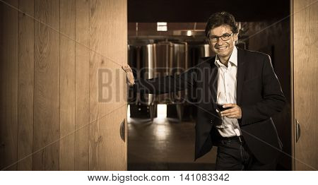 Portrait confidant vintner drinking red wine in winery cellar