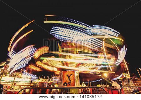long exposure of a fair ride on a warm summer evening toned with a retro vintage instagram filter effect