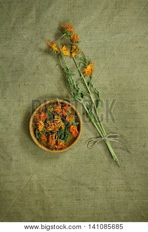 Calendula.Dried herbs for use in alternative medicine.Herbal medicine phytotherapy medicinal herbs.For preparation of infusions decoctions tinctures powders ointments tea.Background green cloth