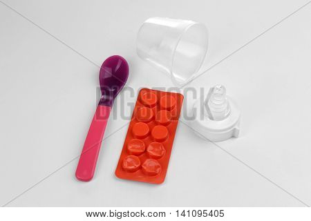 Baby bottle nipple with pills and spoon on white background