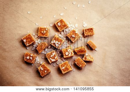 Sweet caramel candies background. Salted caramel pieces and sea salt close up top view over brown baking paper.