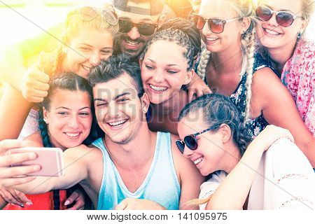 Cheerful group of friends having fun taking selfie at sunset on the beach - Joyful teenagers freezing a moment of celebration during summer festival outdoor - Vintage filter look with sun halo filter