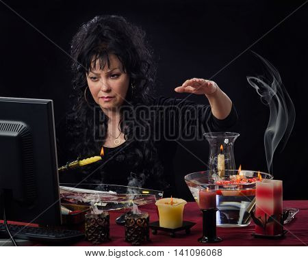 Attractive middle-aged female fortuneteller holds yellow burning candle upright over the water in front of monitor. Psychic in black dress thinks about clients question and wax will begin dripping onto the water soon