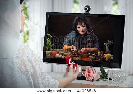 Clairvoyant uses energy of semi-precocious gemstones for charging wedding rings during internet video session. Bride in white dress sits opposite a monitor and holds small red box with two rings. She smiles and looks at diviner