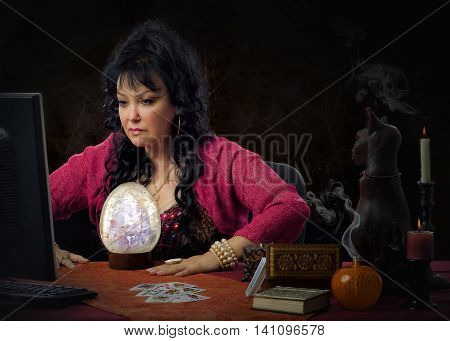 Middle-aged fortuneteller works on-line with big crystal egg. Black haired mature clairvoyant wears dark red linen shrug. The psychic sits at the desk and looks intently to monitor