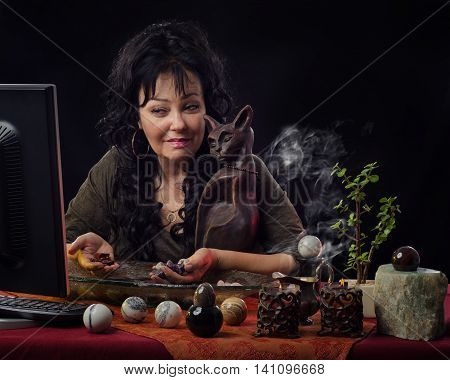 Middle-aged female fortuneteller works on-line with semi-precocious gemstones. Black haired diviner sits at the desk surrounded by different jasper spheres, smoking candles. She holds some gemstones in hands and looks at the monitor. Horizontal indoors sh