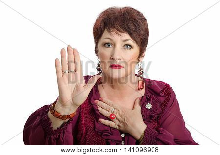 Middle-aged woman with short haircut raises right palm and looks at camera. She either pleads or swears. Horizontal indoors photo on white background