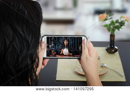 Woman sits at a cafe table and communicates with fortuneteller by mobile phone. In touchscreen, the clairvoyant is predicting the future using a crystal egg