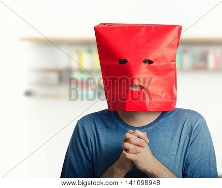 Shy young man feels awkward. Introverted  guy wears red paper bag over head.  Upper body shot