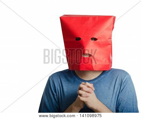 Shy guy with clenched hands wears red paper bag over head because he is lacking in confidence.  Upper body portrait on white background