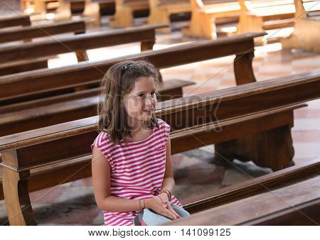 pretty little girl on Pew in the church during a prayer