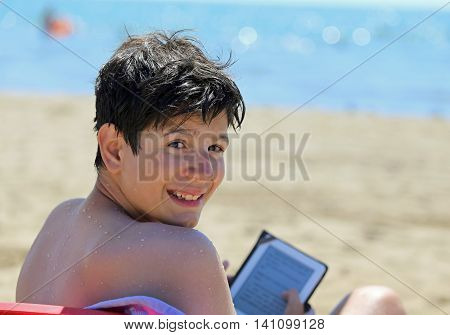 smiling young boy reads the ebook on the beach in summer