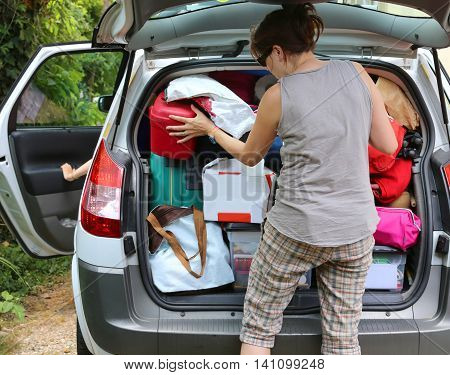 young mother loads the luggage in the trunk of the car before departure poster