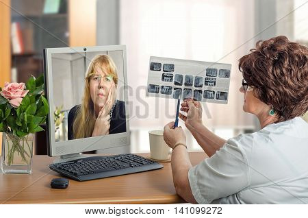 Dentist examining young woman during online video session. Virtual doctor in white uniform looks at x-ray image of teeth. Long haired blonde girl has a toothache. She suffers pain in monitor