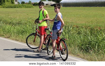 two brothers by bike on the bike path during a trip