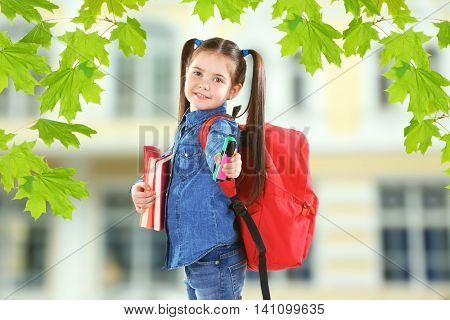 Little girl with red back pack holding books and stationery on blurred school building background