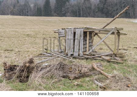 Destroyed raised hide on a meadow in the winter