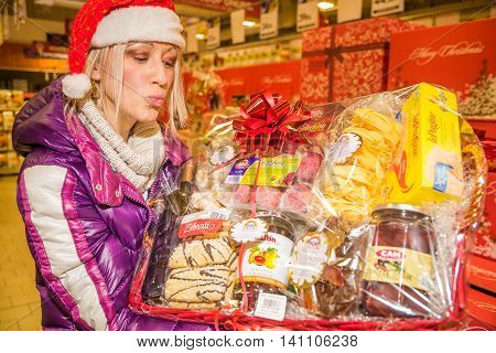 Bologna, Italy - December 13, 2014: Woman showing typical italian nationwide food products in for sale only during Christmas weeks. Pasta, Lasagne, regional bisquists, marmelade, mustard, cold cuts