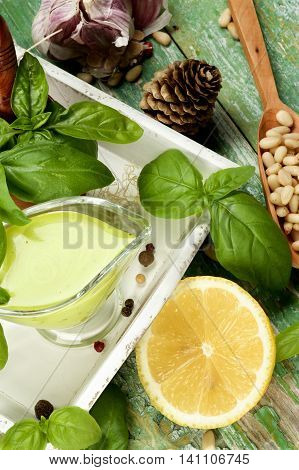 Freshly Made Creamy Pesto Sauce in Glass Gravy Boat with Ingredients in White Wooden Tray closeup Cracked Wooden background