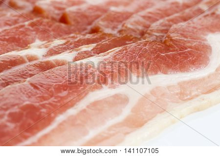 Detail Of Strips Of Streaky Uncooked Bacon Isolated On White.