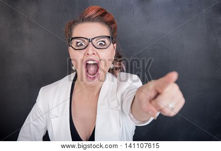 Angry Screaming Teacher Pointing Out On Blackboard Background
