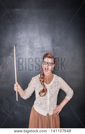 Angry Screaming Teacher With Pointer On The Chalkboard Background