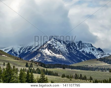 Cloudy landscape with snowy mountains and fields