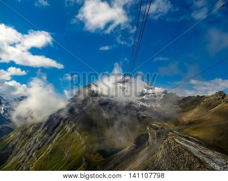 Mountain range with cables going up into the snowy peak