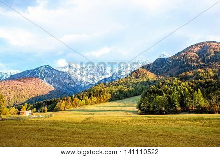 Beautiful landscape view with green field and snowed up mountains in Triglav national park in Slovenia. Traveling slovenian Alps