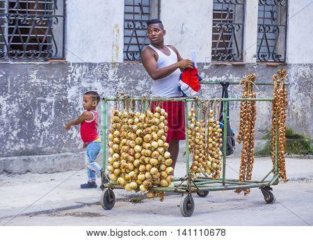 HAVANA CUBA - JULY 18 : A Cuban onions seller in old Havana street on July 18 2016. The historic center of Havana is UNESCO World Heritage Site since 1982.