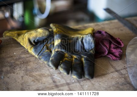 Dirtied welding gloves rest on workbench as laborer breaks for lunch.