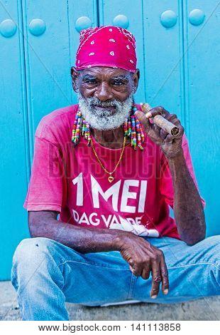 HAVANA CUBA - JULY 18 : A portrait of a Cuban man smoking cigar in old Havana street on July 18 2016. Cuba now exports more than 90 million cigars a year