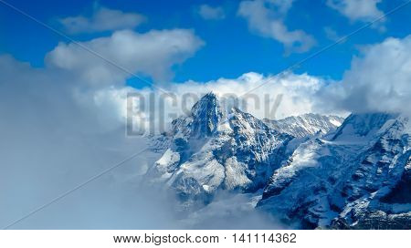 Snowy mountain range surrounded by clouds in winter