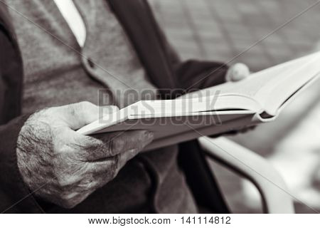 closeup of an old caucasian man reading a book outdoors, in black and white