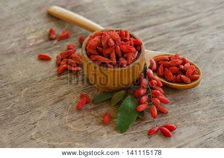 berberries near goji berries heap and wooden spoon bowl with goji on wooden background