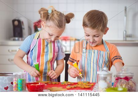 Cute Boy And Girl Preparing Christmas Cookies At Home
