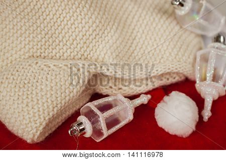 Knitted hat with ear-flaps on the background of Santa Claus xmas red hats and Christmas decorations
